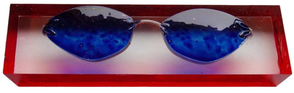 Blaue Brille auf Plexiglas-Sockel