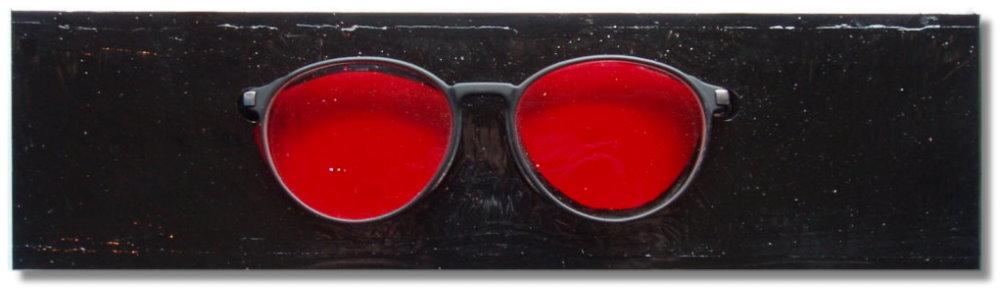 Rote Brille auf schwarzem Sockel